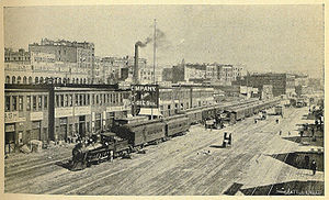 Regrading in Seattle - Railroad Avenue, today's Alaskan Way, depicted here in 1900, was built on fill from the early regrades. To the right in this picture, casting shadows, are the wharves of the Central Waterfront.