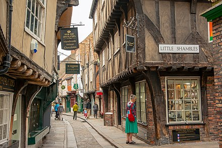 The Shambles is a medieval shopping street in the city; most of the buildings date from between c. 1350 and 1475 Shambles shopper 8686.jpg
