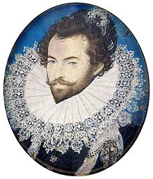 A head-and-shoulders portrait of Sir Walter Raleigh.  He is wearing an extremely large ruff, and has his hair done up in curls. Underneath the ruff, he is wearing a black shirt.
