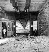 A square opening forms the entrance to the bridge's lower level. Vertical wooden supports line the level. Flagstones pave the entrance and a booth stands to the left. A man stands at the booth, another sits in front of the entrance, and another is walking up the stairs on the right.