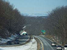 Looking downslope along a divided highway in winter with mountains in the distance