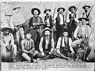 "Battle of Tres Jacales - Company D, Texas Rangers, at Ysleta in 1894. ""Wood"" Saunders is sitting third from left, Carl Kirchner is sitting to the right of Saunders and Captain John Hughes is seated in a chair at the far right."