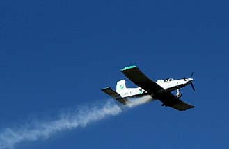 Aerial topdressing -  A PAC Cresco aircraft in action, with the fertiliser emerging from between the wings.