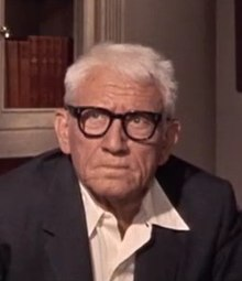 Image of Spencer Tracy with white hair, wearing thick-rimmed glasses and looking grumpy.