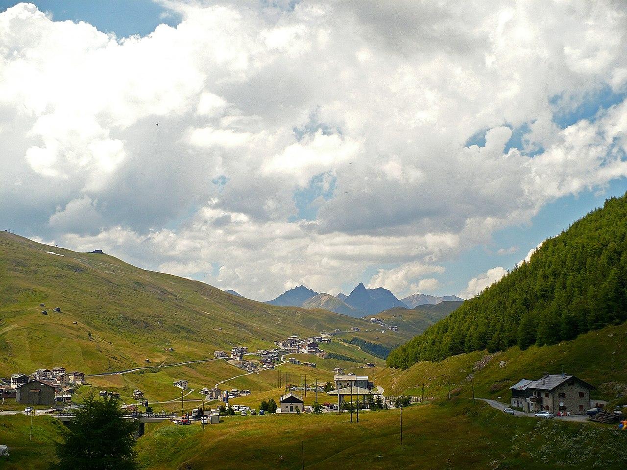Una valle con rilievi vicini e in lontananza cime più alte, in primo piano delle casette