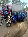 Tricycle in Arua District with cyclist and lorry.jpg