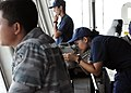 U.S. Coast Guard Ensign Meilyn Quitiquit, right, assigned to the national security cutter USCGC Waesche (WMSL 751), looks through an alidade as an Indonesian navy vessel prepares to sail alongside Waesche 120605-N-KB052-094.jpg