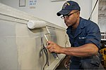 U.S. Navy Boatswain's Mate Seaman Keolis Stephens paints a storage locker aboard the amphibious assault ship USS Bonhomme Richard (LHD 6) in the Coral Sea July 29, 2013, during Talisman Saber 2013 130729-N-BJ178-007.jpg