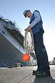 US Navy 030829-N-3228G-003 Gas Turbine Systems Technician Fireman Alan Marlin gathers up the heaving line after mooring the amphibious assault ship USS Peleliu (LHA 5).jpg