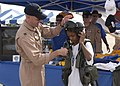 US Navy 030906-N-1522S-080 Lt. Jon Biehl helps a young boy put on a helmet and harness.jpg