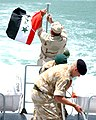 US Navy 040524-N-0401E-004 A British Royal Navy Sailor and Royal Marine coil a line on the deck while U.S. Navy Boatswain's Mate 1st Class Ron Schuetz raises an Iraqi flag on the fantail of Iraqi Patrol Craft 101.jpg