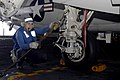 US Navy 040618-N-9228K-023 Airman Jesus Cervantes, assigned to USS Abraham Lincoln (CVN 72), prepares to remove tie down chains on the landing gear of an E-2C Hawkeye.jpg