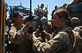 US Navy 040706-N-7586B-079 Cpl. Patricia Ruiz and Lance Cpl. Brandy Guerreo help load weapons and gear down the chain, to the rear of the Landing Craft Utility LCU.jpg
