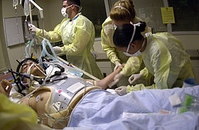 Health care providers attending to a person on a stretcher with a gunshot wound to the head. The patient is intubated, and a mechanical ventilator is visiblein the background.