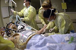 Health care providers attending to a person on a stretcher with a gunshot wound to the head; the patient is intubated, and a mechanical ventilator is visible in the background