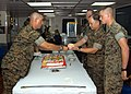 US Navy 041109-N-9860Y-006 U.S. Marine Corps Staff Sgt. Mark Collins, of Williamsburg, Va., left, presents the traditional second piece of cake to the oldest Marine, Col. Rick De Guzman, during a cake-cutting ceremony.jpg