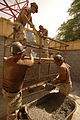 US Navy 050621-N-4309A-007 Seabees assigned to Naval Mobile Construction Battalion Five (NMCB-5) pass concrete in buckets in support of a new public works building at Navy Support Activity (NSA) Bahrain.jpg