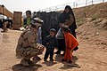 US Navy 070327-N-4928M-006 The Navy Provisional Detainee Battalion Chaplain, Cmdr. Anne Krekelberg plays with an Iraqi child as he waits at the Camp Bucca Visitors Center to see a relative.jpg