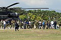 US Navy 100120-N-4995K-178 anadian Soldiers work with U.S. Navy Sailors and Haitian citizens to offload food and water from an MH-53E Sea Dragon helicopter.jpg