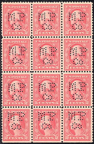 Perfin - A large block of United States perfin stamps.