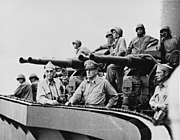 Sailors wearing steel helmets stand by an anti-aircraft gun on a quadruple mount. Two officers lean on the railing, staring off into the distance.