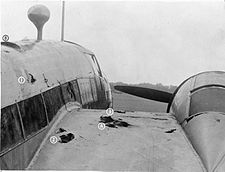 a black and white photograph of a portion of the fuselage and wing of an aircraft with holes that served as foot and hand holds