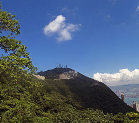A wooded mountain with tall antennas around its summit and medium-height buildings below it. There is a tree on the left of the image, and on the right the mountain slopes down to an area next to water with some taller buildings.