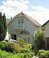 foto van Houten huis met gerabatte wanden met zolderverdieping onder zadeldak met wolfeind