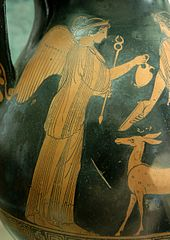 Photo of part of a black vase with brown picture on it: A woman with wings on her back hold an arrow with right hand and gives a jar to a man. A small deer is standing in front of the woman.