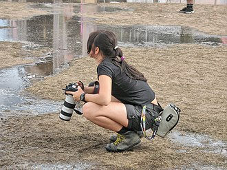 Women in the workforce - A woman press photographer covers a music fest, Poland, 2008.
