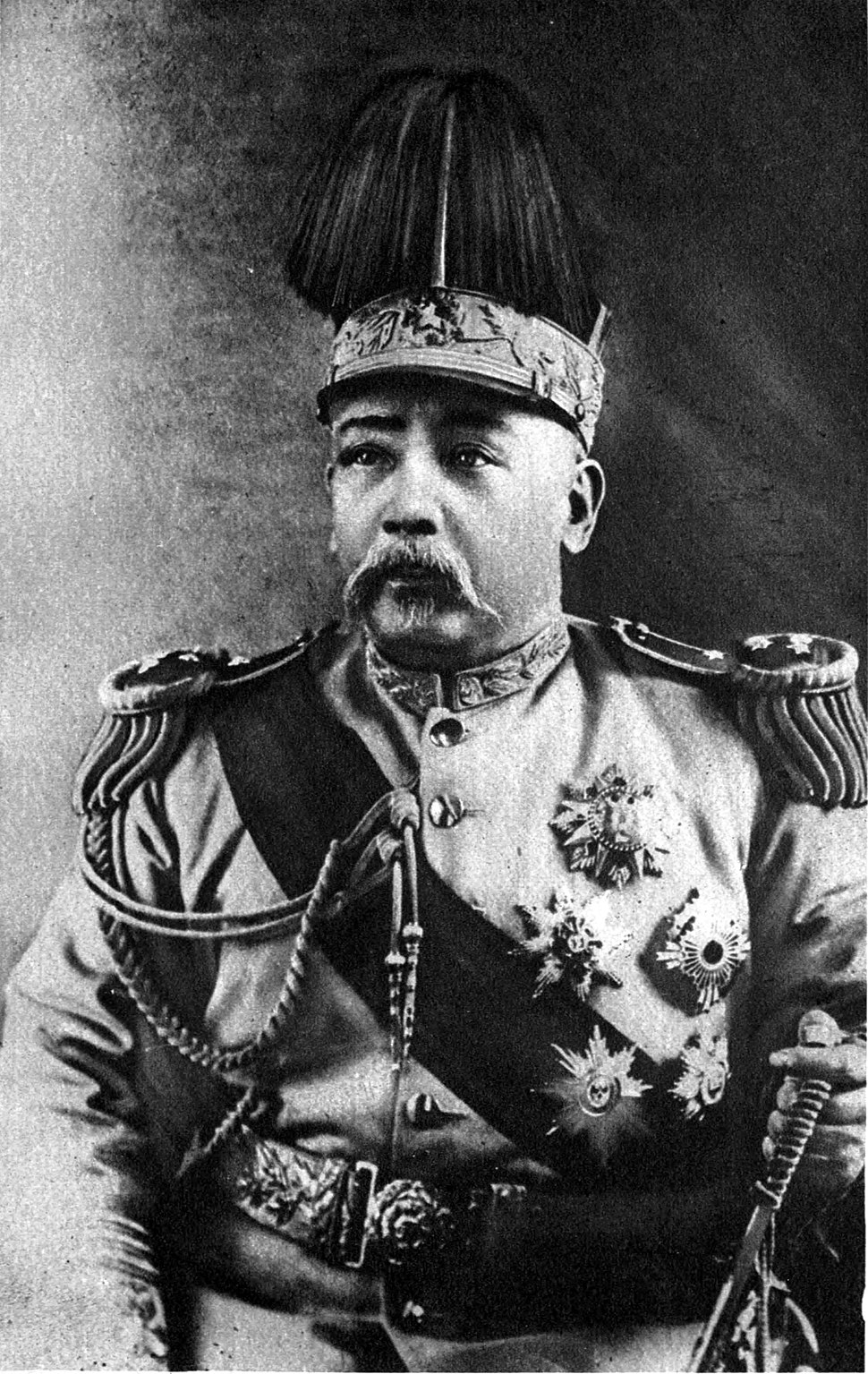 A Chinese man wearing an elaborate military outfit, with a large crown on his head.