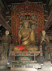 Shown inside the high-ceilinged hall is  a large, gold-colored statue seated cross-legged  on an ornately decorated throne, flanked by two figures in richly coloured robes.