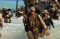 color photo of two columns of Marines wade through waist deep water disembarking from a landing craft onto a beach