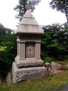 "A granite monument with a pyramidal peak, capped by a maltese cross, etched with an inscription, ""22nd Mass Infantry""."