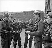 Officer with swagger stick, talking to six other men. In the background are other men and a mountain range