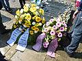 70. Jahrestag der Befreiung des KZ Bergen-Belsen, 26. April 2015 Gestecke an der Gedenkwand von HuK und Befah.JPG
