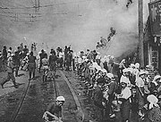 Black and white photo of women standing on a street passing buckets along a chain of people towards a building on fire. Other people are climbing a ladder from the street into the building.