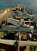 Several aircraft with wings folded parked near the bow of an aircraft carrier. Several men surround the aircraft, and steam is issuing from the carrier's catapult.