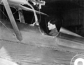 Side view of dark-haired man in open cockpit of biplane equipped with machine-gun on upper wing