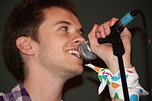 A close-up photograph of Alex Day singing into a microphone, taken from below.