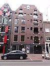 Dubbel pakhuis met trapeziumgevel, gevelsteen en jaartallinten