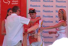 A cyclist is presented an orange jersey, and is in the process of donning it. A man wearing white is facing the cyclist and pulling the jersey's sleeves forward around him. Two women in white dresses flank the cyclist.