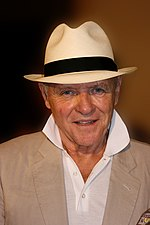 A man wearing a black and white hat including a beige suit and white shirt.