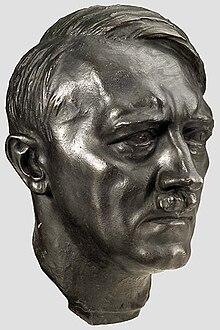 Photo en couleurs (fond gris clair) d'une tête en bronze d'Adolf Hitler, réalisée par le sculpteur Arno Beker, en 1398.