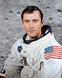 Portrait photograph of Young in an Apollo spacesuit in front of a lunar surface background