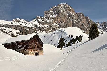 Barn on the Mastlé mountain. In the background the Pitla Fermeda and Gran Fermeda peaks in the Puez-Geisler Nature Park in the Dolomites UNESCO World Heritage Site.