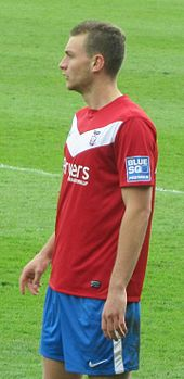 A man with brown hair who is wearing a red top, blue shorts and white socks. He is standing on a grass field.
