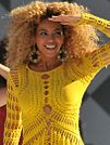 Woman with blonde curly hair wearing a yellow outfit