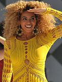 A woman with blonde hair wearing yellow outfits and smiling