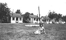 Black-and-white photograph of a woman sitting on grass infront of a row of cabins